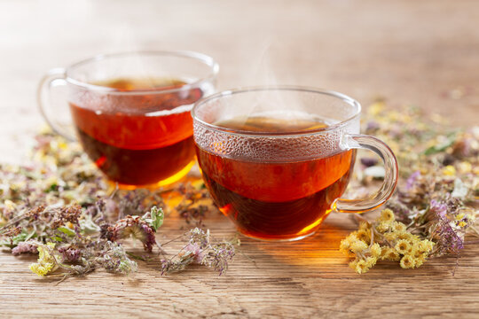 Cups of herbal tea with dried herbs