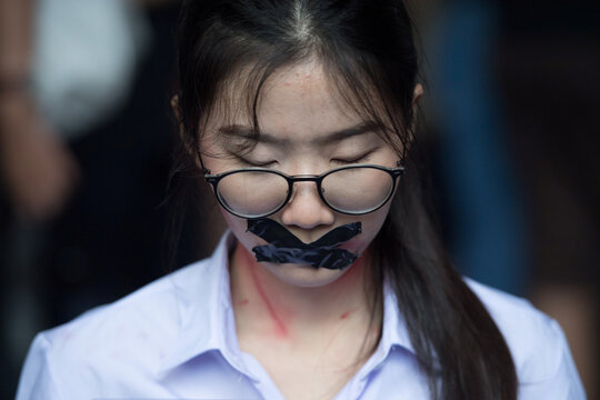 Nalinrat Tuthubthim, 20, a student, who claims she was sexually abused by a teacher, has her mouth covered with tape during a rally in Bangkok