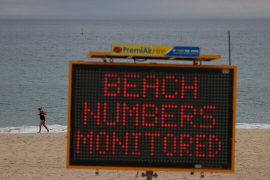 A jogger exercises beyond a COVID-19 public health warning sign at Bondi Beach in Sydney