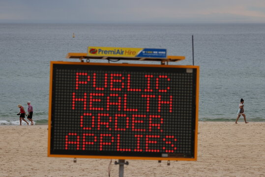 People walk by the ocean beyond a COVID-19 public health warning sign at Bondi Beach in Sydney
