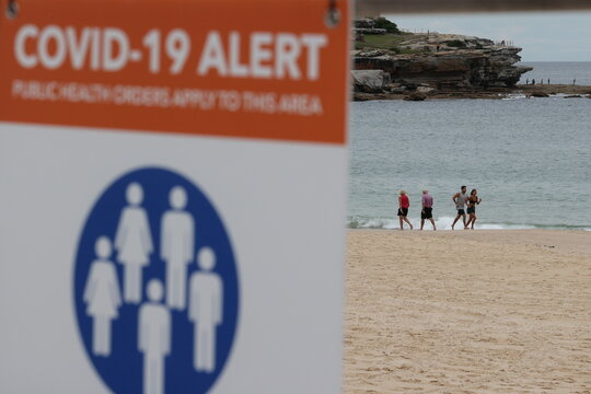 People are seen by the ocean beyond a COVID-19 public health warning sign at Bondi Beach in Sydney