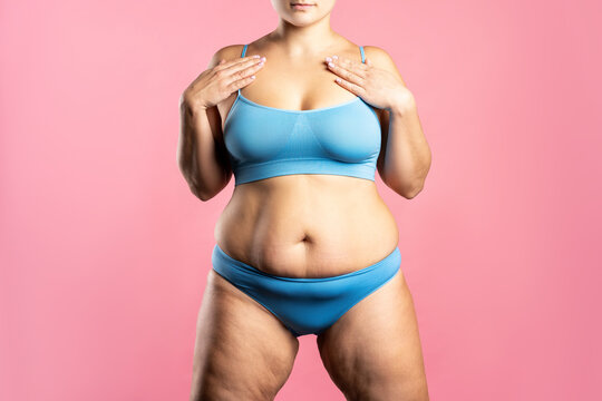 Fat woman in blue underwear on pink background, overweight female body
