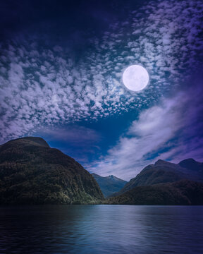 Mysterious Moon brightening the night at Doubtful Sound a fjord in the very remote wilderness in New Zealand, South Island. An overnight cruise is a fantastic experience lost in the natural world and