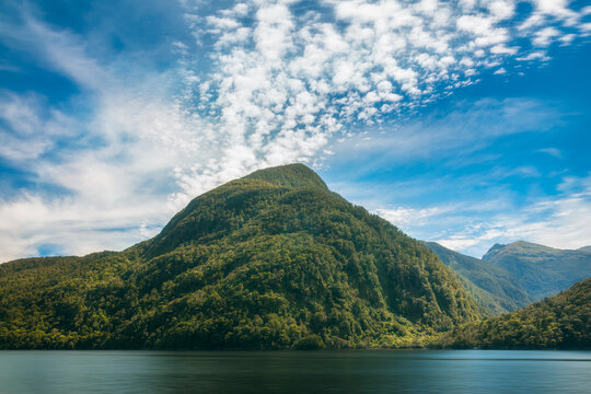 Spectacular clouds emerging from the mountain top on a fresh morning in the wilderness at Doubtful Sound, a fjord in New Zealand, South Island.