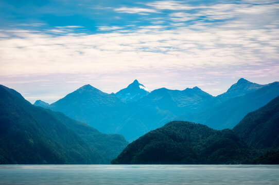 Morning Aurora (dawn light) rising behind the mountains in the wilderness of the Deep Cove at Doubtful Sound, a fjord in New Zealand, South Island.