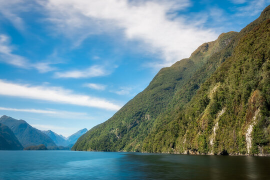 Mountain range covered in rainforest and water views in the remote wilderness of Deep Cove at Doubtful Sound in New Zealand, South Island.