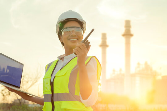 asian female engineer technician Industrial workers wearing safty uniform with walkie-talkie and laptop working inspection in a power plant background