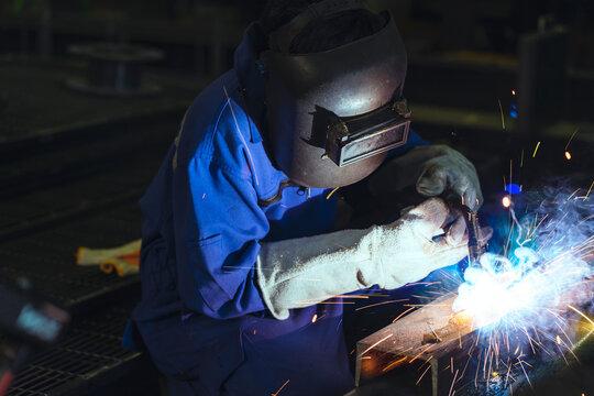 asian male technician worker in a dressed in protective uniform welding metal frame wear welders leathers,Electric welding on steel structure in factory workshop