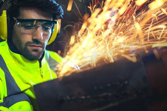Caucasian male worker in a safty uniform wear welders leathers,Electric wheel grinding on steel structure in factor in the garage, orange bokeh sparks fly to the sides