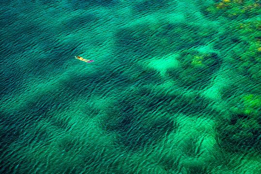 Frau schnorchelt in türkis blauem Meer
