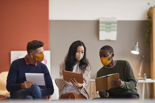 Multi-ethnic group of three business people wearing face masks while discussing project in office