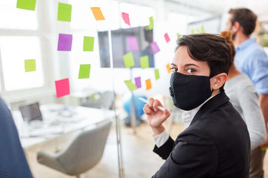 Business Frau mit Maske im Brainstorming Workshop