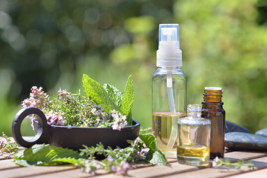 bottle of essential oils spilled on a  table with  lavender flowers on green bokeh background