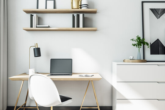Cozy home office desk with laptop and supplies.