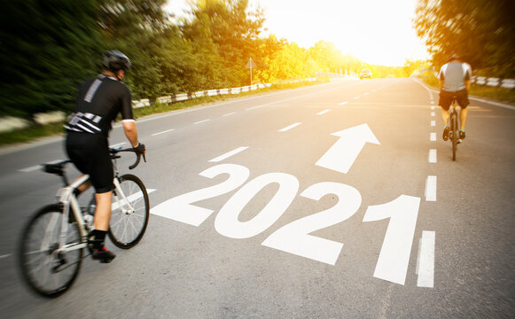 Two cyclist is moving straight to the 2021 year