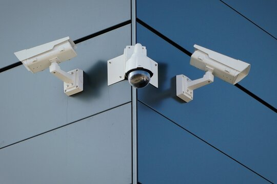 Low Angle View Of Security Cameras On Blue Building