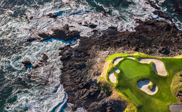 Drone view of a golf course next to the ocean at low tide with waves hitting the rocks in Pebble Beach