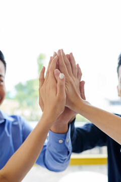 Close-up image of business people giving each other high five after finishing work on big project