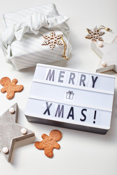 New Year or Christmas composition, flat lay, top view. Light box inscription Merry Christmas, gifts in Japanese furoshiki style and gingerbread cookies, copy space.