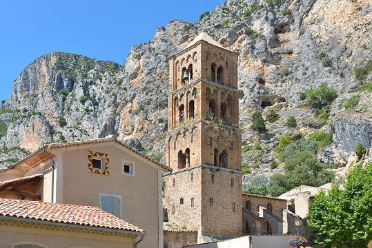 Moustiers-Sainte-Marie at the foot of the mountain and church of Notre-Dame-de-l'Assomption with its square bell tower . Moustiers-Sainte-Marie is a commune in the Alpes-de-Haute-Provence department