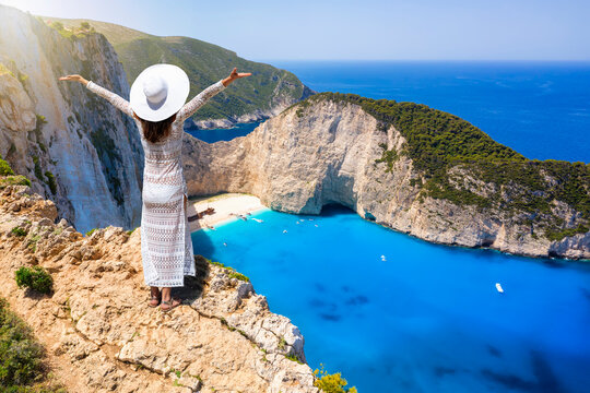 A happy tourist woman in a white summer dress and with hat enjoys the spectacular view to the famous shipwreck beach, Navagio, on the island of Zakynthos, Greece