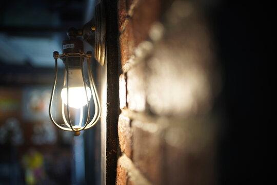 Close-up Of Illuminated Light Bulb By Wall