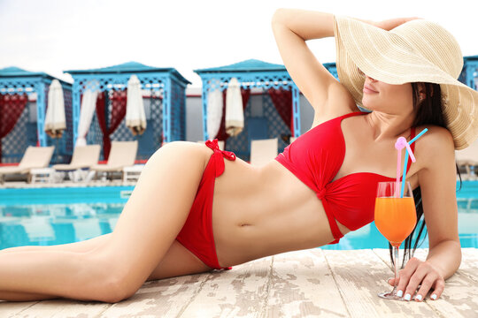 Young woman in stylish red bikini with cocktail near swimming pool