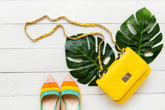 Fashion bag and shoe woman accessories wood white background. Trendy fashion luxury yellow handbag, shoe design with monstera leave green.