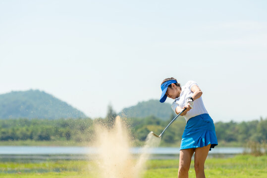 Golfer woman chip golf ball out of a sand trap. People swing and hitting golf course is on the fairway.  Hobby in holiday and vacations on club golf.