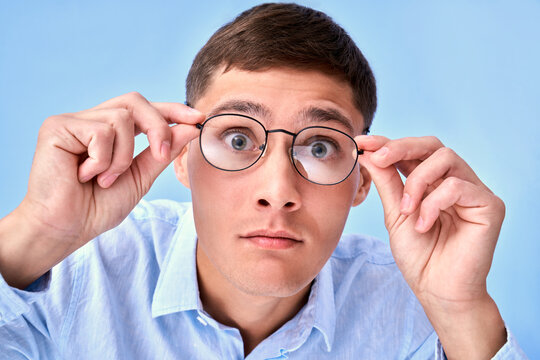 OMG! Studio shot shocked caucasian man holds hands on the rim of glasses, cant believe his eyes, curious look at camera, emotional reaction to unexpected news isolated on blue background