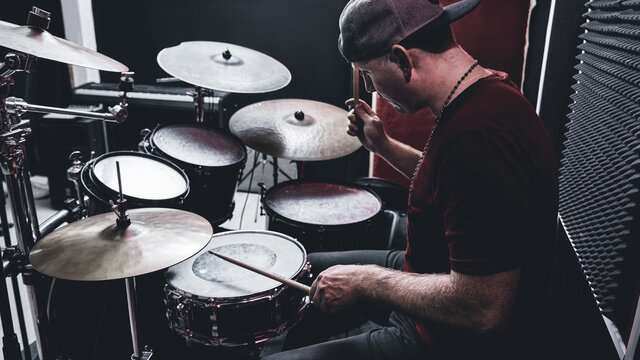 Modern professional drummer plays drums at a rehearsal base, red and black recording studio