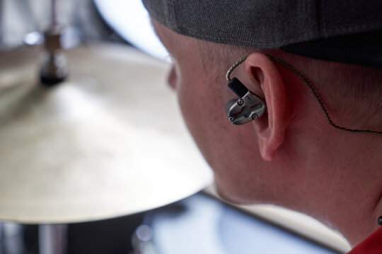 Drummer plays drum kit with a special in-ear intracanal earphone for musicians close-up