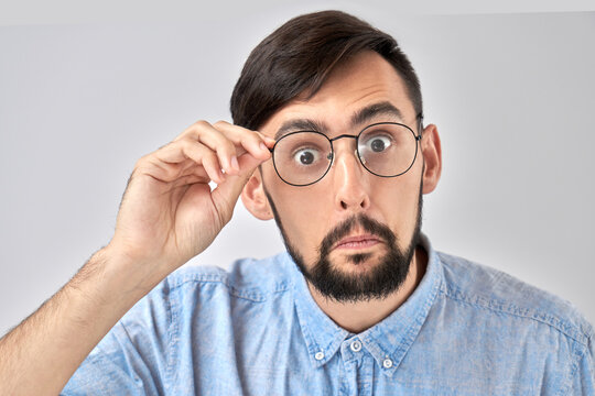 Wow! Caucasian bearded man with bulging eyes and a surprised face holds hands on the rim of glasses and looks at the camera, emotional reaction to unexpected news isolated in blue studio