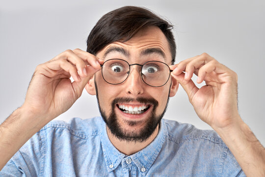 OMG! Wow! Caucasian bearded man with happy smiling face holds hands on the rim of glasses, cant believe his eyes, curious look at camera, emotional reaction to amazing news isolated in blue studio