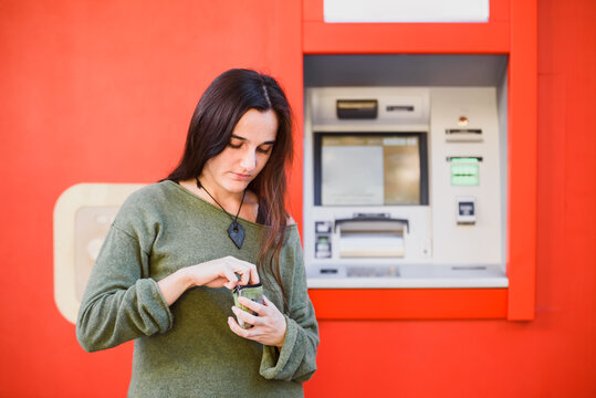 A young woman in front of an ATM searches her purse for some coins.