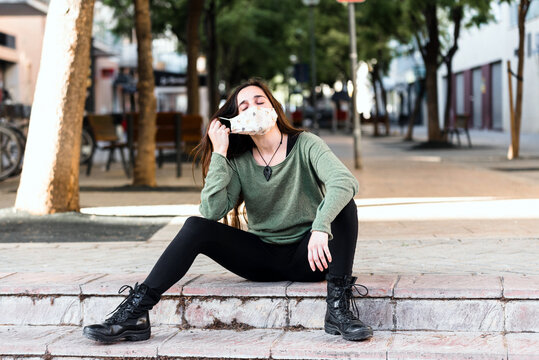 Young woman removes mask from her face with relief before the end of the pandemic