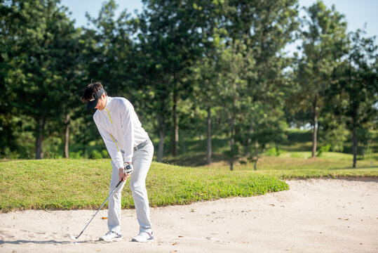 Asia Golfer man hitting out of a sand trap. The golf course is on the sand.  Hobby in holiday and vacations on club golf.