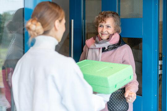Volunteer delivering a meal to door of senior citizen