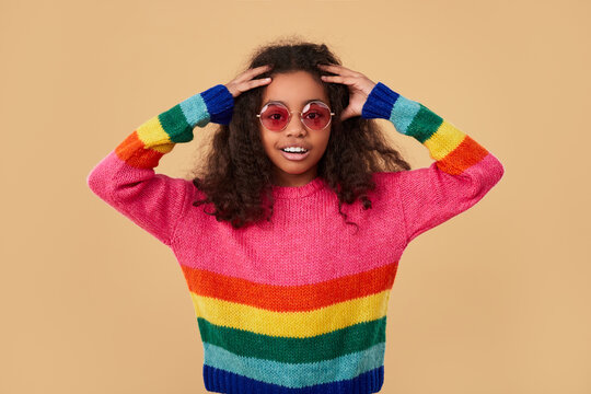 Excited hipster girl in colorful sweater and sunglasses