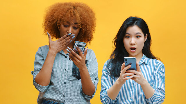 Two young women checking social networks and showing their surprise with wierd face expression. High quality photo