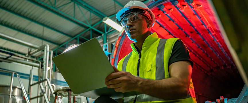 Chief Industrial Engineer in Hard Hats used Laptop Computer check and control machine while Sitting in the Heavy Industry Manufacturing Factory.man at work and maintenance engineer concept.