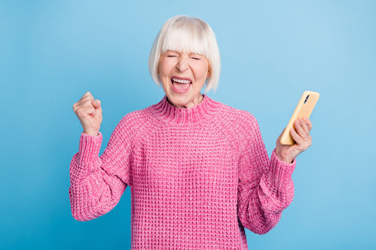 Photo portrait of crazy screaming old woman holding phone in one hand isolated on pastel blue colored background