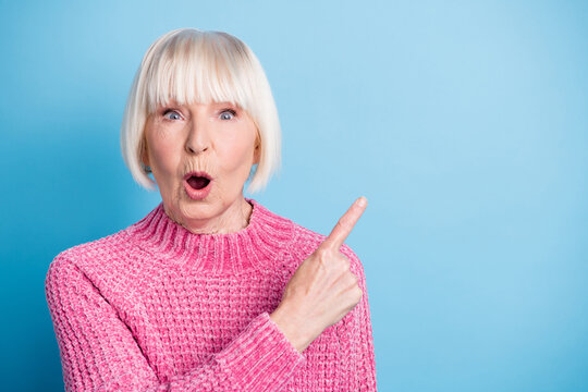 Photo portrait of amazed elderly lady pointing finger at blank space isolated on pastel blue colored background