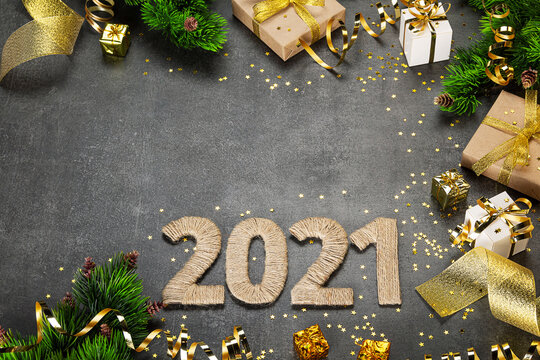 Happy new year 2021. Bright card with golden serpentine and ribbons, christmas gifts on dark background