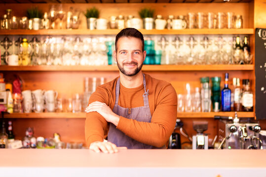 Small business owner man standing in the restaurant and waiting for guest. Portrait shot of handsome waiter wearing apron and smiling while standing behind the counter in the cafe