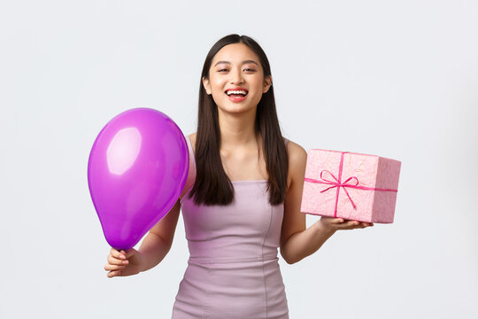 Celebration, party and holidays concept. Cheerful asian girl in evening dress, enjoying birthday, having fun, holding balloon and gift, laughing carefree, standing white background