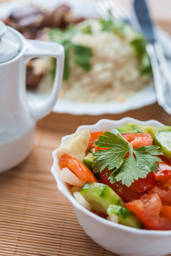 Salad of tomatoes and cucumbers on bamboo tablecloths. Mashed potatoes with parsley and porcine liver.