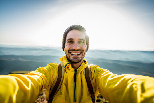 Happy hiker taking a selfie on the top of a mountain - Smiling man smiling looking camera - Handsome male face outdoor