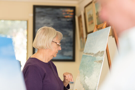 Elderly woman in art class with painting