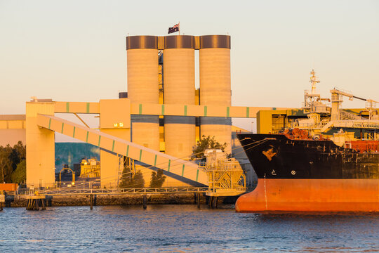 The bow of a ship docked near tall grain silos at the Port of Brisbane